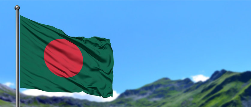 Bangladesh flag waving in the blue sky with green fields at mountain peak background. Nature theme.