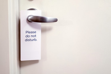 Closed white door of hotel room with please do not disturb sign