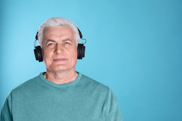 Mature man enjoying music in headphones on color background. Space for text