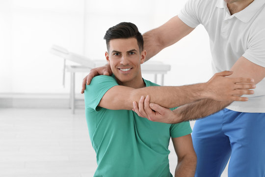 Professional physiotherapist working with male patient in rehabilitation center
