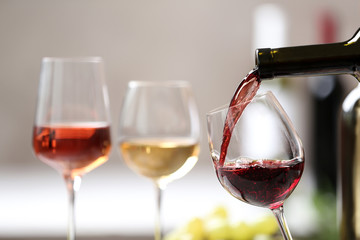 Spoed Foto op Canvas Alcohol Pouring red wine from bottle into glass on blurred background. Space for text