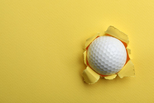 Torn color paper with golf ball, space for text. Sport equipment