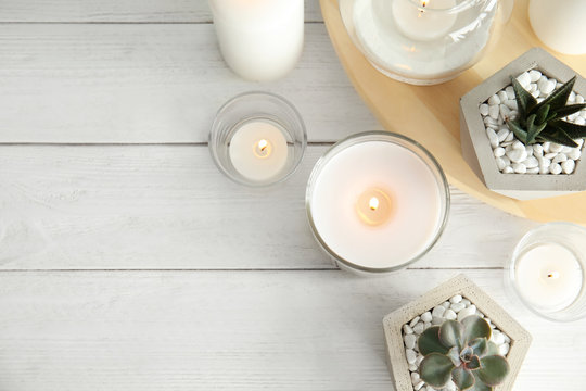 Flat lay composition with burning aromatic candles and plants on wooden table. Space for text