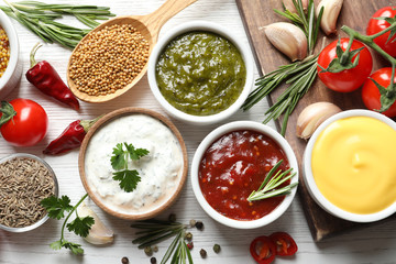 Flat lay composition with different sauces and ingredients on white wooden background