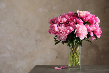 Fragrant peonies in vase on table against color background, space for text. Beautiful spring flowers