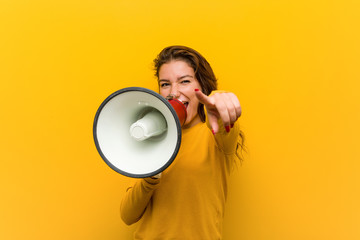 Young european woman holding a megaphone cheerful smiles pointing to front. Wall mural