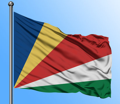 Seychelles flag waving in the deep blue sky background. Isolated national flag. Macro view shot.