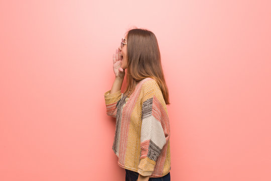 Young hippie woman on pink background whispering gossip undertone