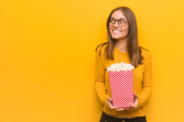 Young pretty caucasian woman smiling confident and crossing arms, looking up. She is eating popcorns. Wall mural