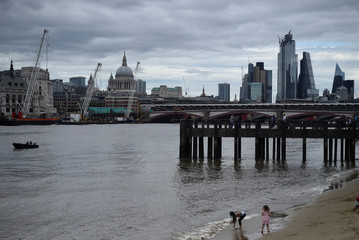 Children play on a beach along the Thames river with St. Paul's Cathedral visible in the background in London