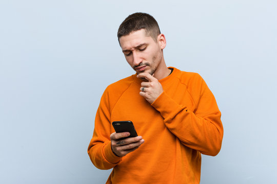 Young caucasian man holding a phone looking sideways with doubtful and skeptical expression.