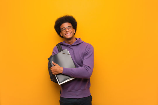 Young african american student man smiling confident and crossing arms, looking up