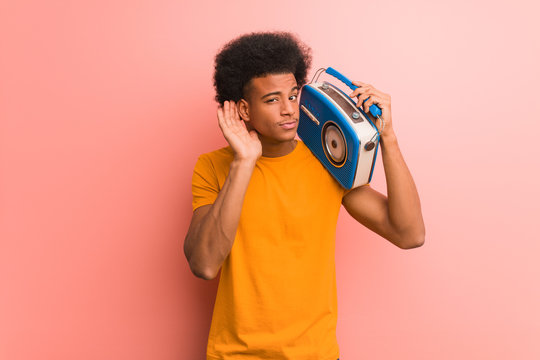 Young african american holding a vintage radio try to listening a gossip
