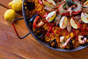 Delicious Spanish seafood paella, view from above. Cooked with sturgeon halibut fillet, peeled shrimps squids, mussels and lobster decorated with lemon slices red bell pepper in pan, close up image .