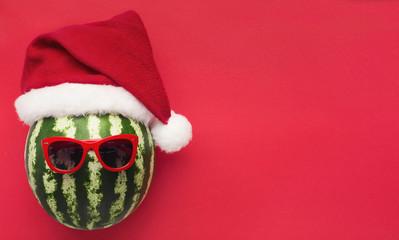 Striped watermelon in Santa hat and sunglasses