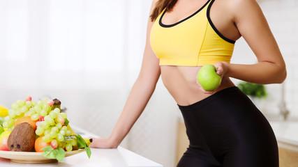 Slim Girl Eating Fruits For Breakfast In Kitchen