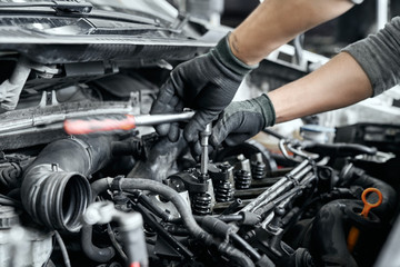 Close up of man's hands using wrench to remove spark plugs Fotomurales