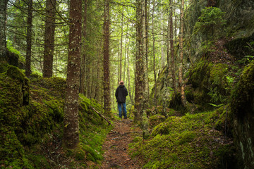 Man with hat and jacket standing in a forest clearing. Oslo, Norway.