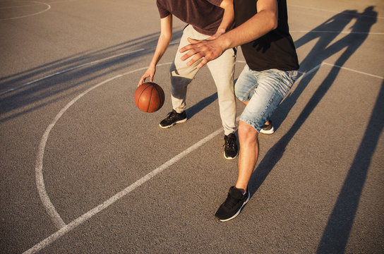 Unrecognizable young people playing basketball , sunset