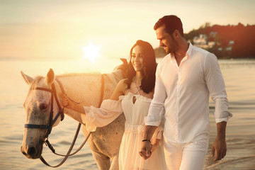 Photo sur Plexiglas Artiste KB Young couple walking a majestic horse - seaside landscape