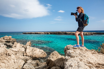The young woman the traveler with a backpack and in a dress costs with the camera on the bank of the beautiful blue sea. It takes the picture.
