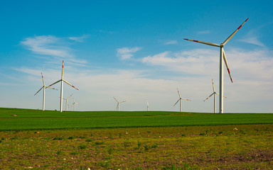 Wind turbines and agricultural fields on a summer day - Energy Production with clean and Renewable Energy