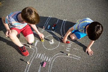 Two brothers sibling kid boy having fun with picture drawing traffic car with chalks. Creative leisure for children outdoors in summer. Difficult traffic rules education friendship concept