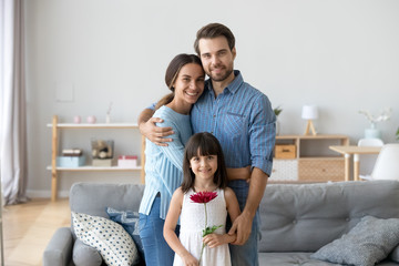 Portrait of happy parents hug posing with cute daughter