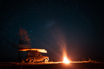 Night landscape with bright campfire and car