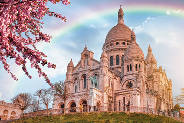 View of Basilica Sacre Coeur in Montmartre in Paris, France. Spring time with cherry blossom tree and blue sky with rainbow.