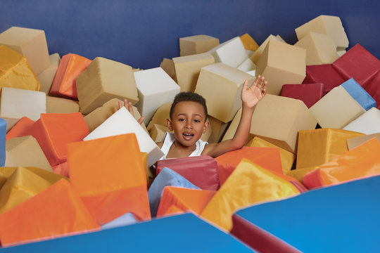 Portrait of cheerful energetic Afro American little boy having fun in trampoline park at weekend, playing with colorful soft cubes, saying Hello, waving hand. Entertainment, recreation and childhood