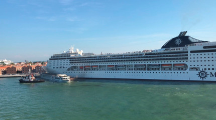 A huge cruise ship MSC Opera crashes into a dock and a tourist riverboat on a busy canal in Venice
