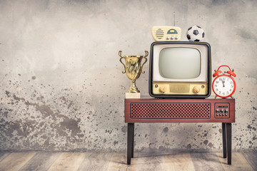 Retro outdated television from 50s, soccer ball, golden winner cup, radio receiver, orange alarm clock on wooden TV stand front aged textured concrete wall background. Vintage old style filtered photo