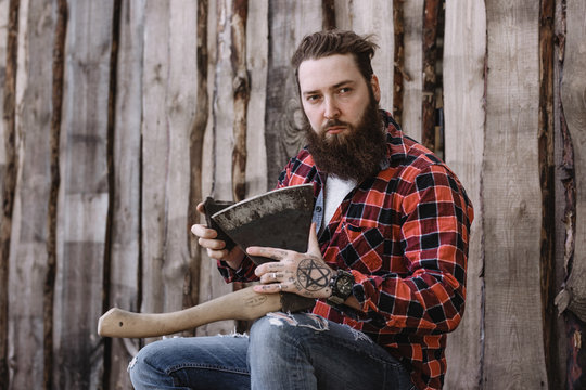 Brutal strong man with a beard dressed in a checked shirt and torn jeans is sitting and sharpening ax in the hands against the background of a wooden fence