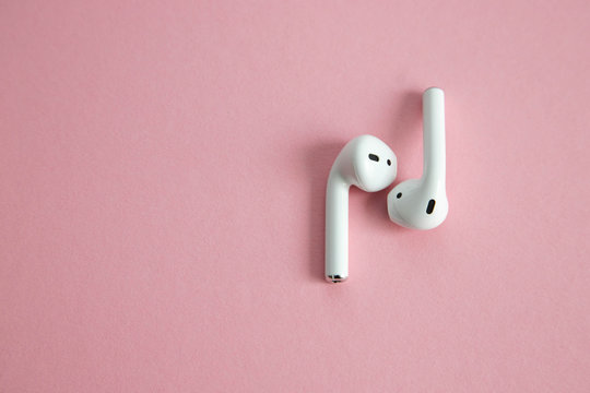 wireless white headphones without cord, lying next to each other on a pink background. Place for text