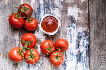 Fresh tomatoes on a branch and tomato sauce on a rustic background. Flat lay food. Wooden vertical frame