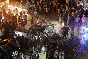 People gather at the site of a car bomb blast in Azaz