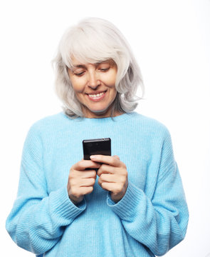 Lifestyle, tehnology and people concept: old woman wearing casual talking on cell phone over white background