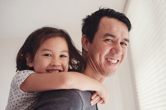 Happy multicultural Asian daughter with her father at home, Father's Day