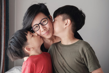 Two sons kissing their mother at home, Happy Asian family portrait