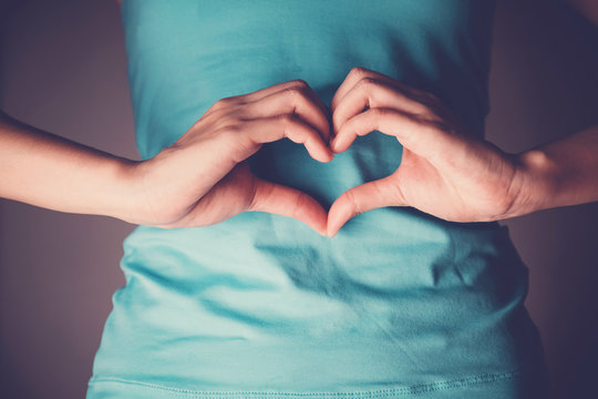 Woman hands making a heart shape on her stomach, healthy bowel degestion, probiotics  for gut health, leaky gut, Sign Language