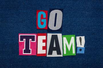 GO TEAM text word collage, multi colored fabric on blue denim, teamwork concept, horizontal aspect