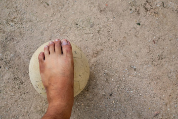 Close up picture of an old ball and foot of a boy who is playing football