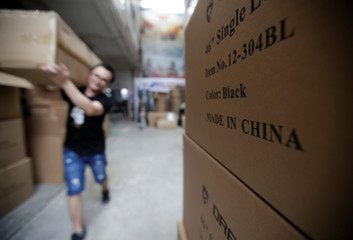 "Boxes of gun cases with the words ""Made in China"" are placed in a factory of firearm equipment manufacturer Yakeda Tactical Gear Co, which exports most of its products to the United States, in Guangzhou"