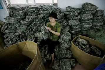 A woman works on military bags on the production line of a factory of firearm equipment manufacturer Yakeda Tactical Gear Co, which exports most of its products to the United States, in Guangzhou