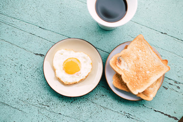 Fried eggs, toast, coffee, breakfast set placed on a blue wooden table