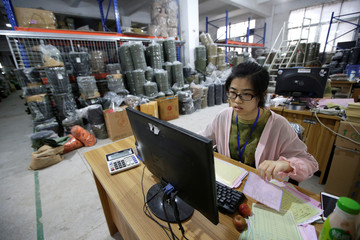 A woman works in the material room of a factory of firearm equipment manufacturer Yakeda Tactical Gear Co, which exports most of its products to the United States, in Guangzhou