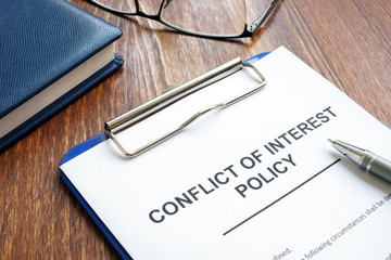 Conflict of interest policy and pen on a wooden surface.