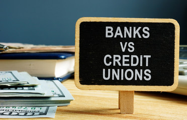 Banks vs Credit Unions concept. Money and ledger.
