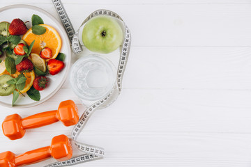 Diet plan, menu or program, tape measure, water, dumbbells and diet food of fresh fruits on white background, weight loss and detox concept, top view Fotobehang